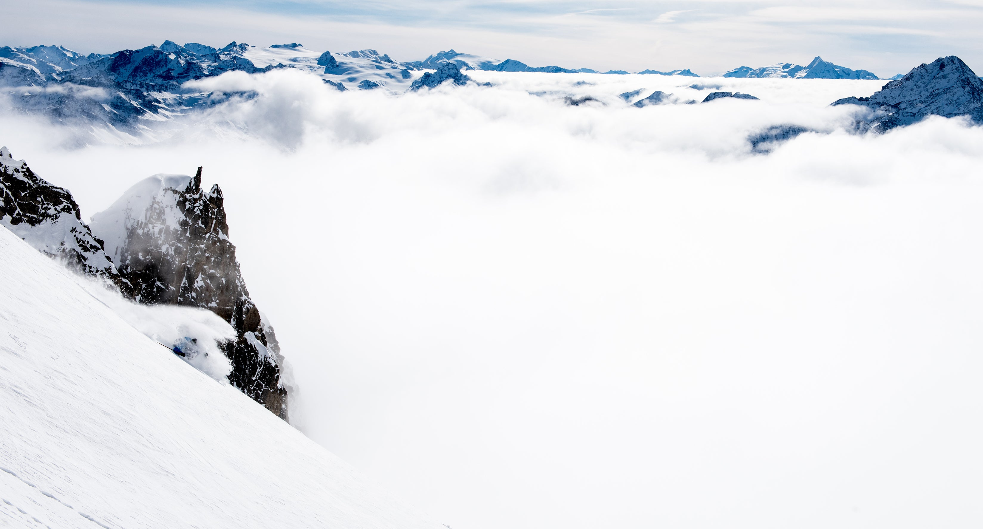 Skier turning above the cloud-covered Italian valley