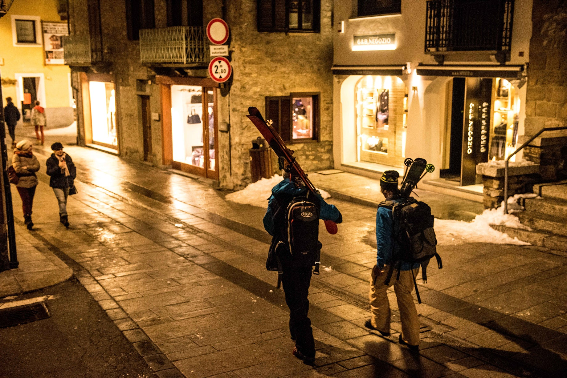 Skiers walking through town at night