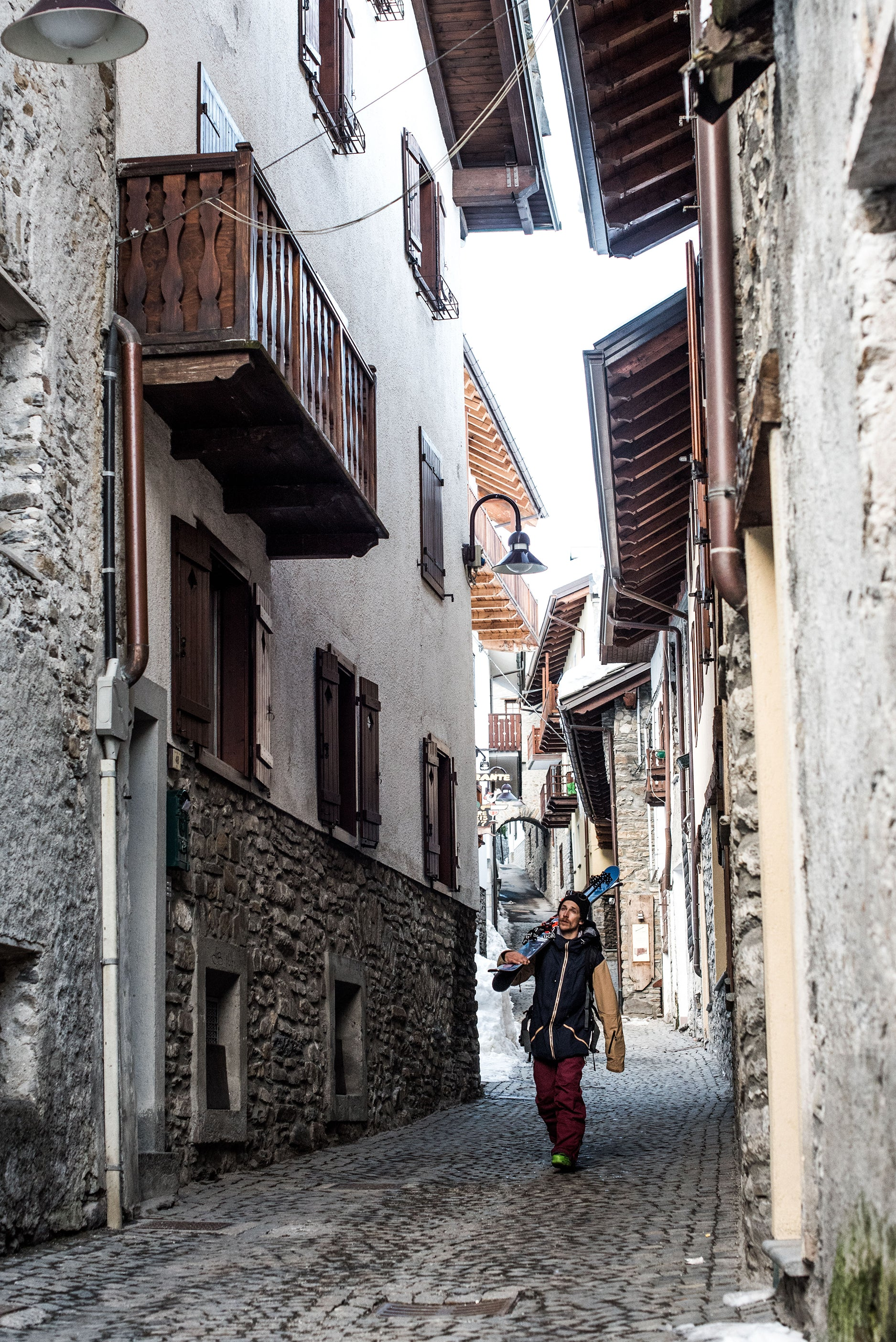 Skier walking over cobbled European streets