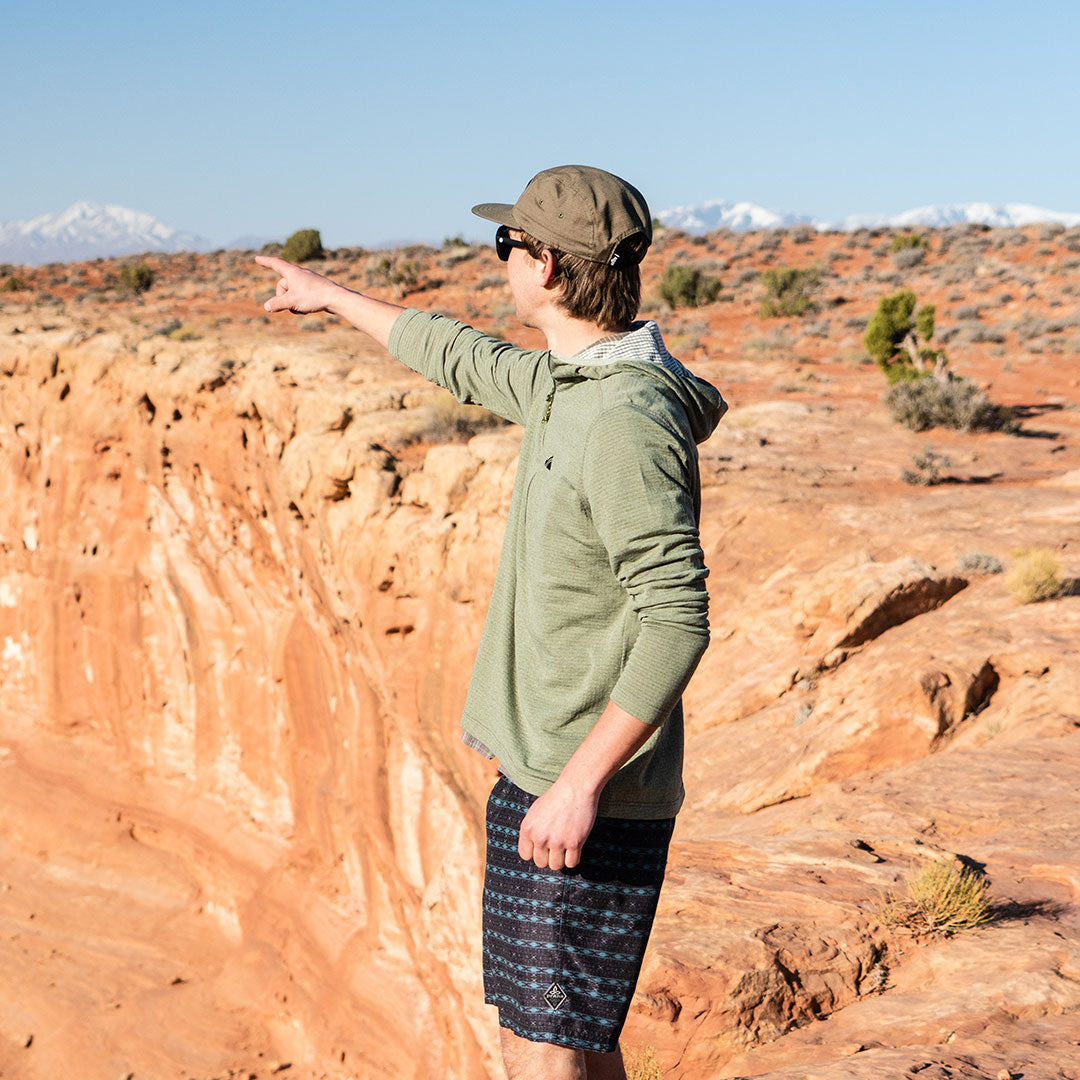 pointing towards skiing from the desert in the olive basecamp hoodie