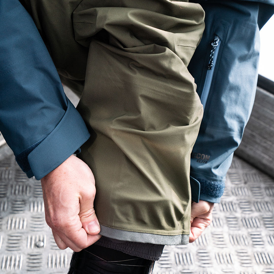 snowboarder fixing cuff in gondola on olive capitol pant