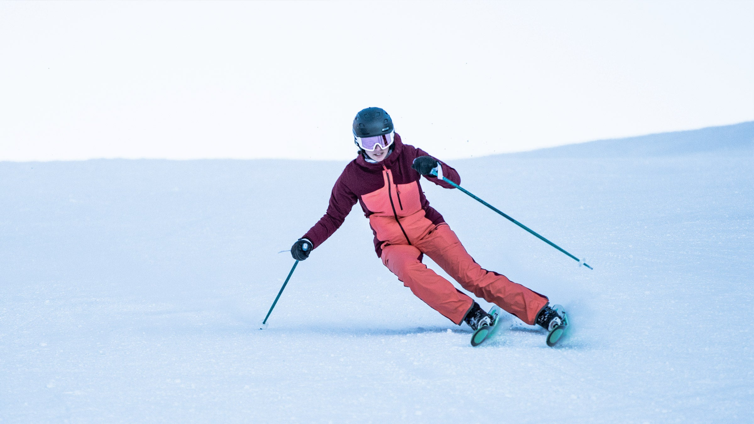 skier carving in eden jacket on aspen mountain
