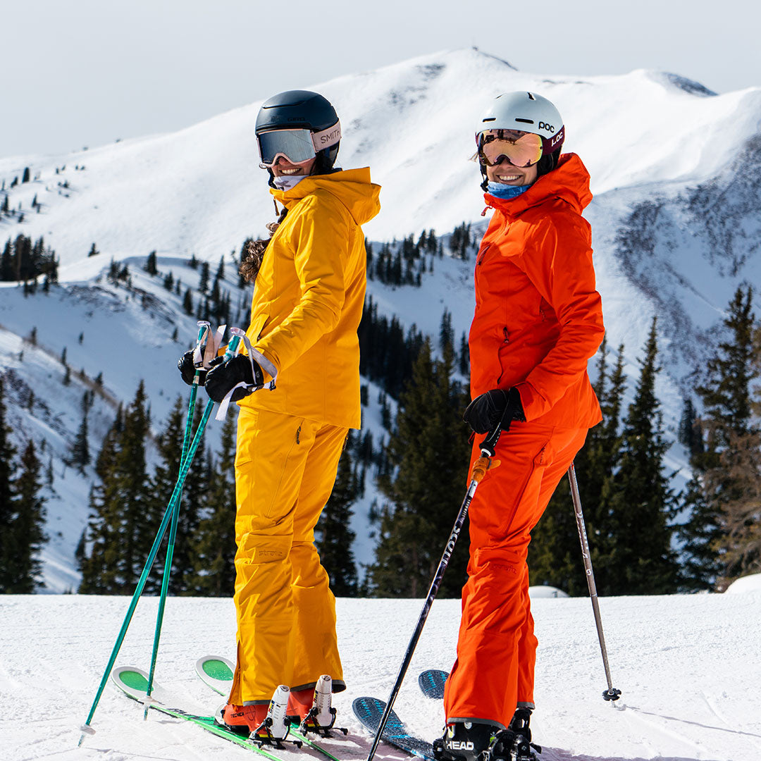 two skiers in front of highland bowl in eden jackets