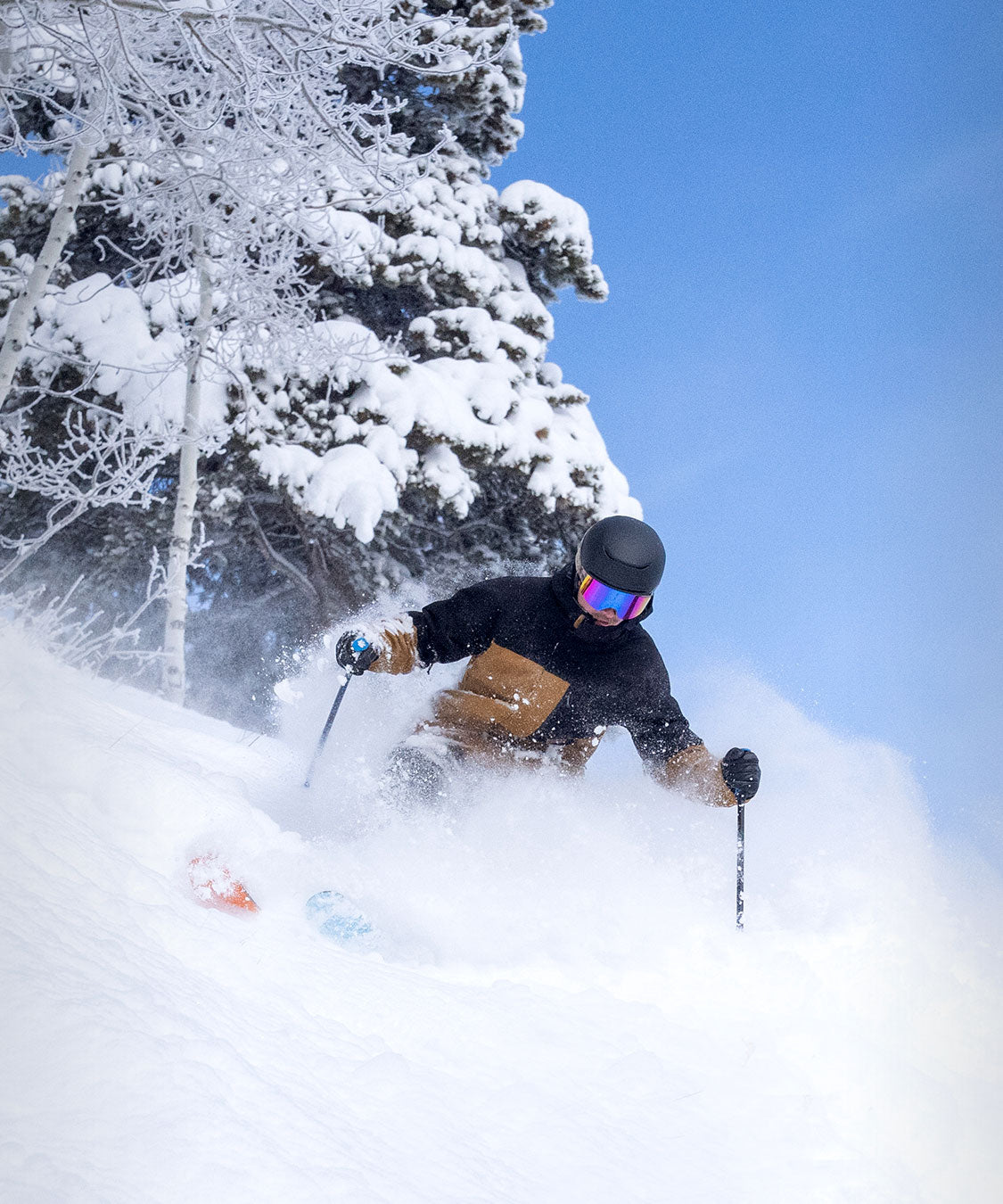 powder turn in the Hayden ski jacket in front of snowy mountains
