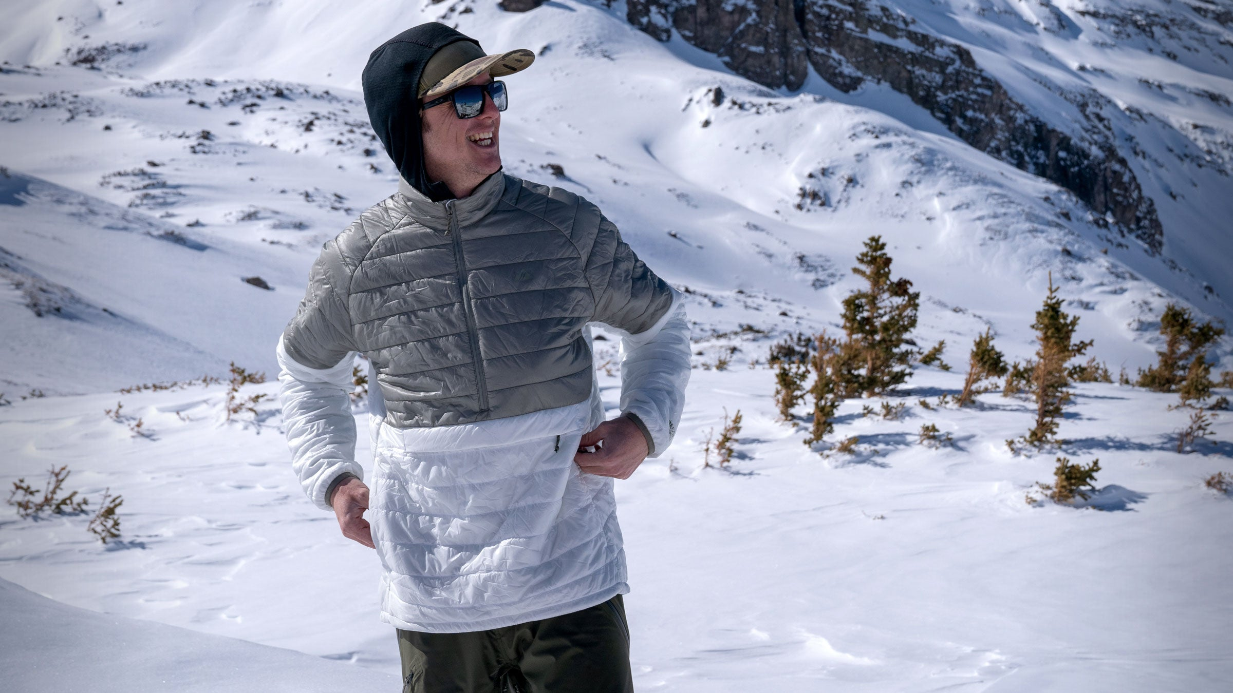 man smiling in aero pullover insulator mid-layer in front of mountains