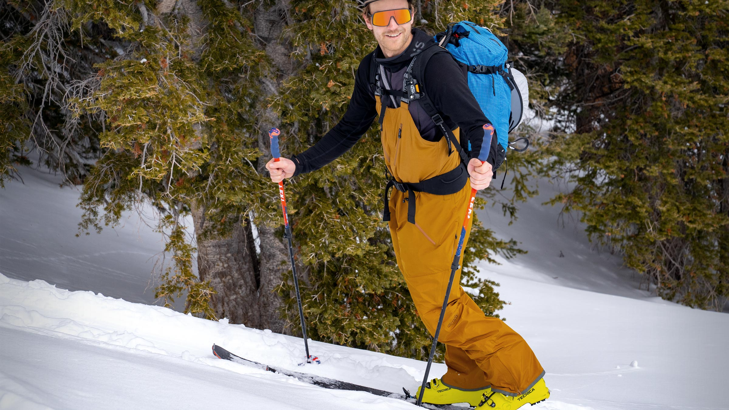 Skinning through evergreens in the nomad bib ski pant