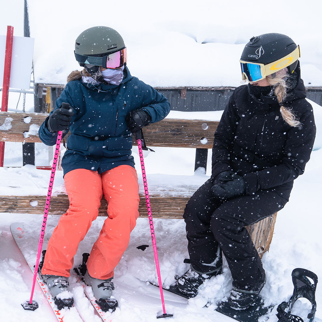 skier and snowboarder sitting on bench in snow in their wildcat pants