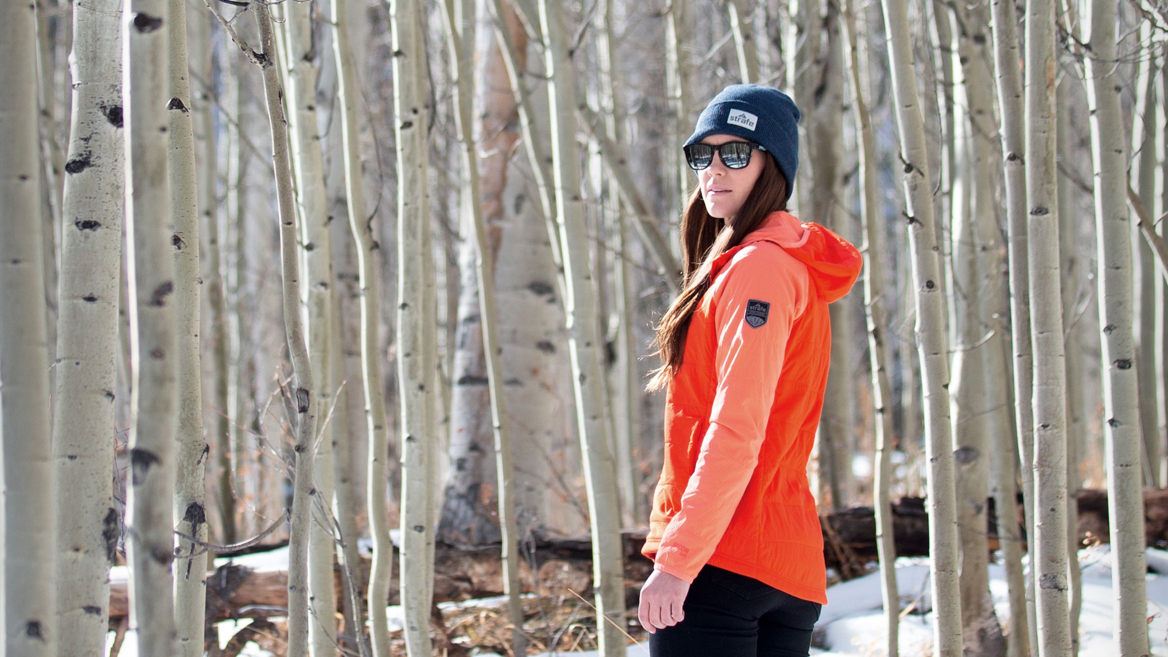 wearing hooded alpha insulator in front of aspen trees
