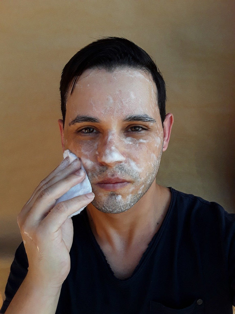 man washing his face with soap