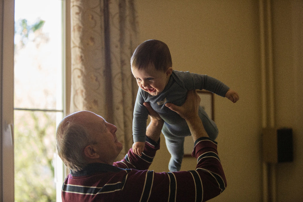 old man holds laughing baby