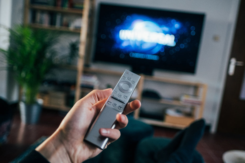 man holding tv remote with blue screen in background