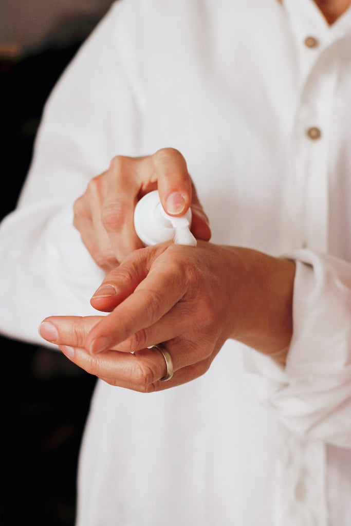 person applying skincare lotion to hands