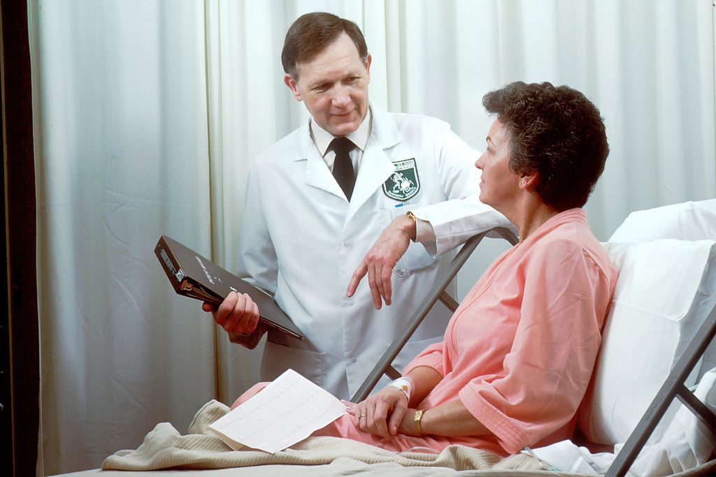 doctor talking to older woman in hospital bed
