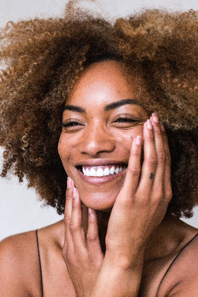 smiling woman touches face