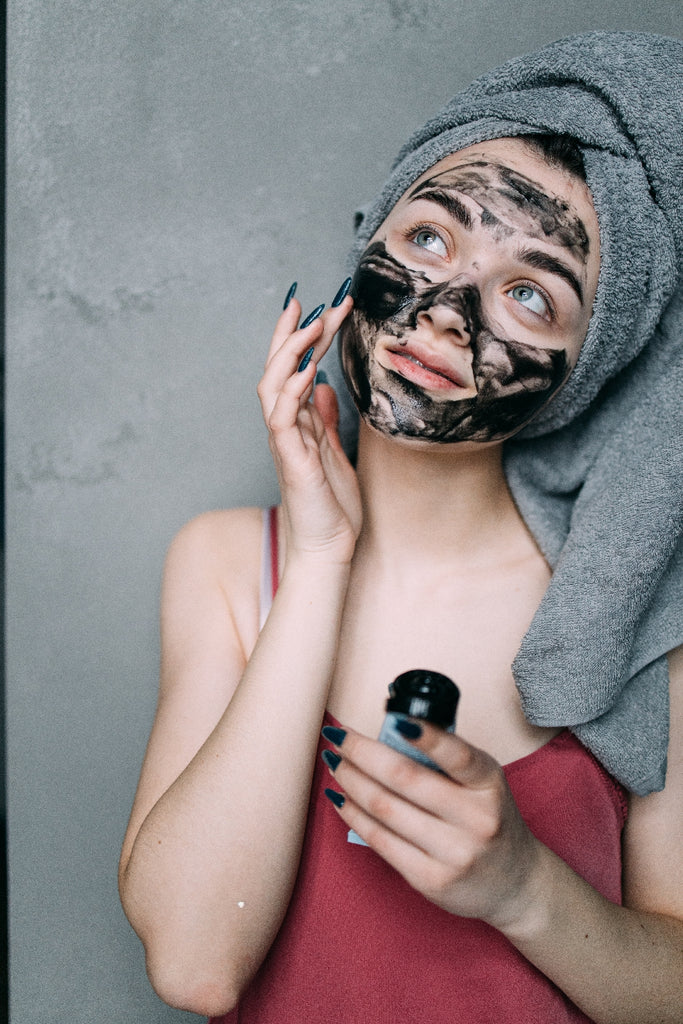woman applying exfoliant to face