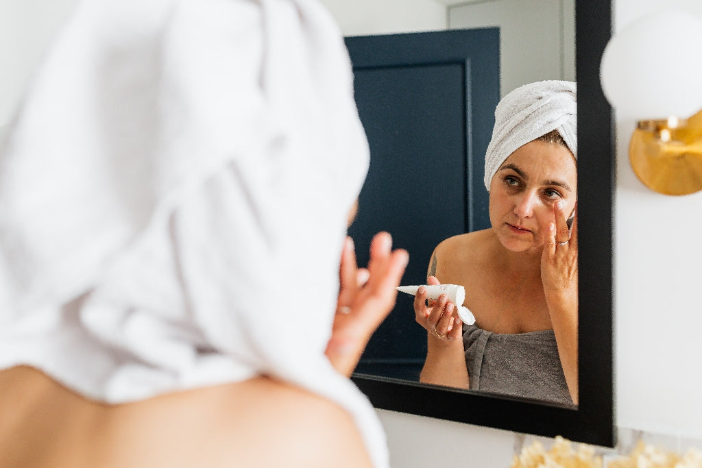 woman applying skincare product before mirror