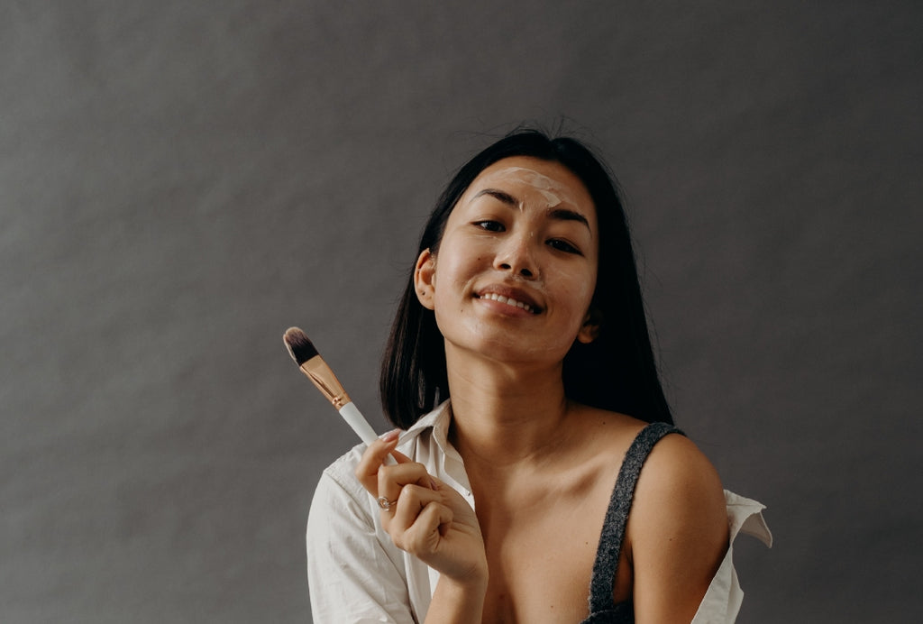 woman using clay face mask holding makeup brush
