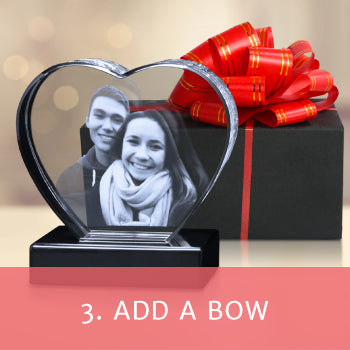 """Crystal heart shaped photo gift on a black base featuring a picture of a couple in front of a black box with a red bow with a red box overlay and text reading """"Add a bow"""""""