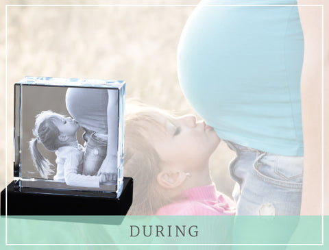 "Little girl kissing pregnant mom's belly with crystal photo gift and text reading ""During"""