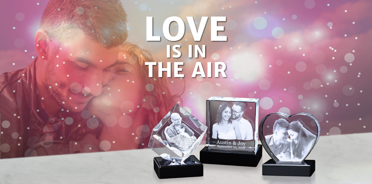 """Background of couple kissing with text overlay reading """"Love is in the air"""" with three crystal photo gifts"""