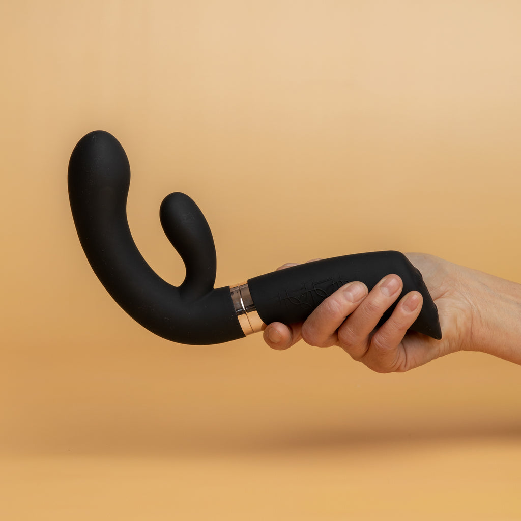 hand holding the enigma sex toy by rocks off. The enigma has an ergonomic thick handle. The middle of the enigma (where you can unscrew it and split it into two parts) is gold. The ergonomic handles relieves pressure on joints and improves accessibility to the enigma sex toy, It is stocked at xesproducts.com.au xes products