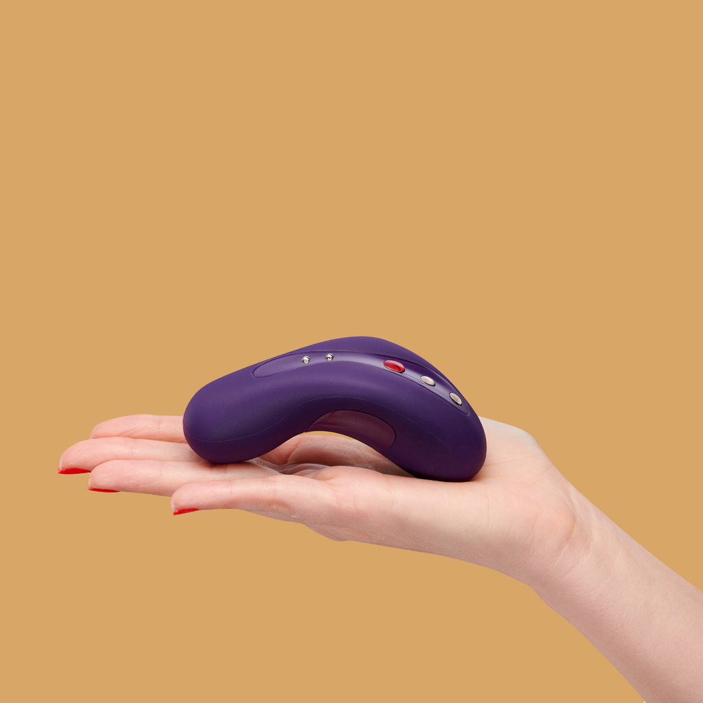 Image of a hand with the Laya 2 by Fun Factory in dark violet resting on top.  That Laya 2 is curved to fit perfectly in the hand with buttons ontop throughout the middle of the toy.