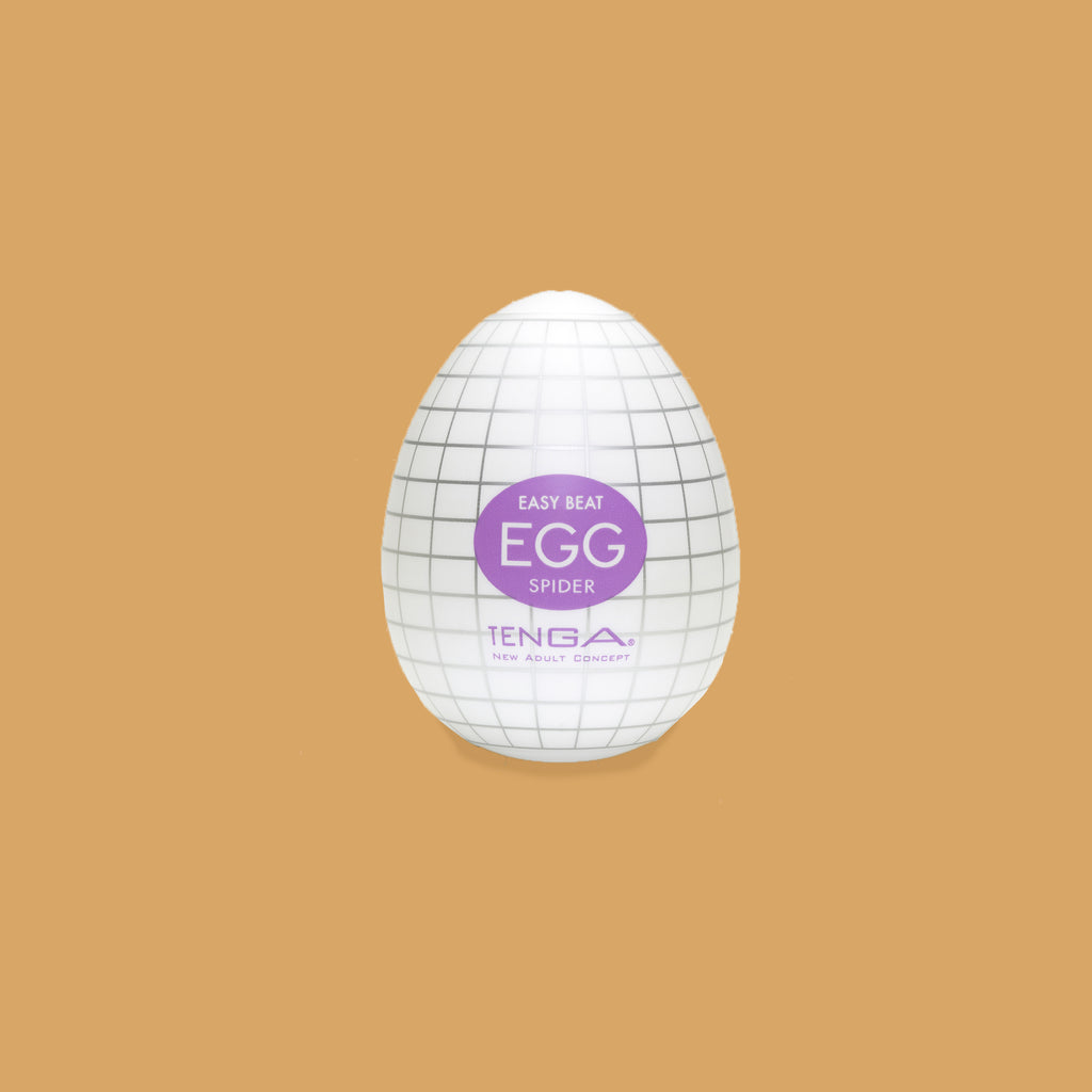 "The Tenga Egg spider packaging. Looks like a hard boiled egg. Colour scheme purple. The spiders patterns looks like squares on a graph otherwise described as ""ribbed spider web pattern"""