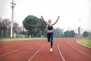 A happy woman on a track after participating in virtual runs in Canada