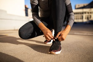 Woman lacing up her shoes to get ready for running events in Canada