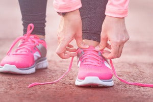 A woman adjusting her shoes, getting ready to start her virtual run in Canada