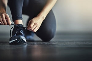 A runner tying her shoes to get ready for virtual runs in Canada