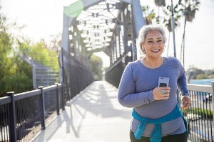 Happy elderly woman running over a bridge during her virtual run event in Canada