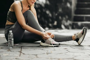A woman tying up her running shoes, getting ready to participate in socially distant races in Canada