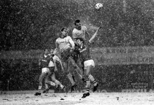 24th January 1984 - League Cup Football - Everton v Oxford United - Paul Hinshelwood and Gary Briggs outjumps Everton striker Adrian Heath in the snow at Goodison.  Photo by Mark Leech / Offside Sports Photography  Limited edition of 100 numbered/embossed prints.
