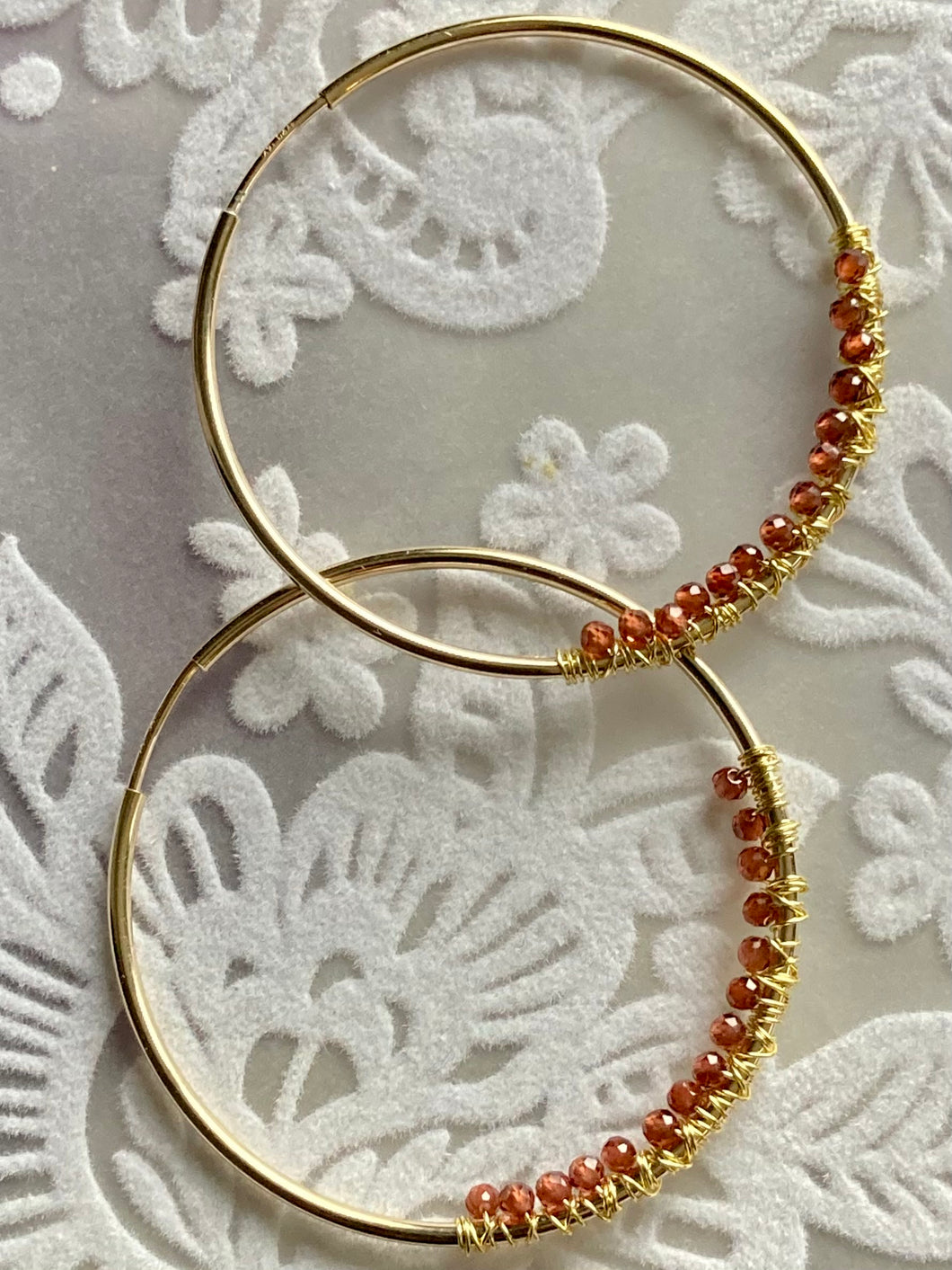 Gold filled 38 mm hoop earrings with wire wrapped teeny garnets