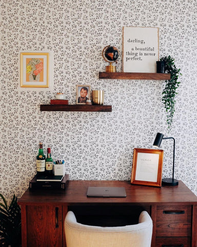 A small home office desk against patterned wallpaper