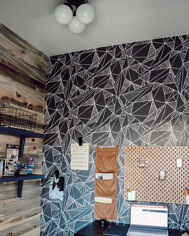 Geometric black and white wallpaper with natural wood tone accent