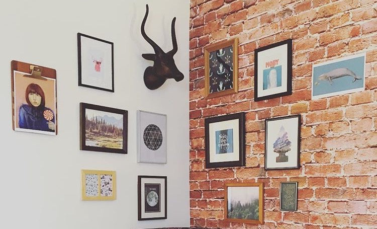 Gallery Wall at WallsNeedLove HQ full of art guys will love!