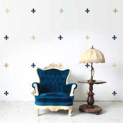 Fleur de Lis wall decal on white wall behind chair | lifestyle