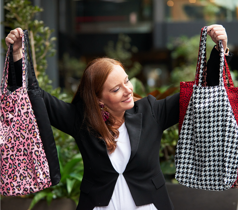 Woman holding up range of colourful Shoezie Shoe Tote bags