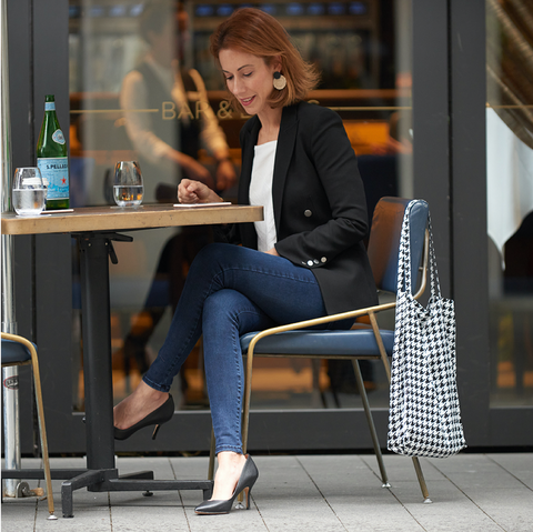 Woman sitting at cafe with Houndstooth Shoezie on back of chair