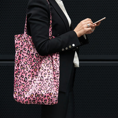 Corporate woman, messaging on phone, carrying Pink Camo Shoezie shoe tote bag