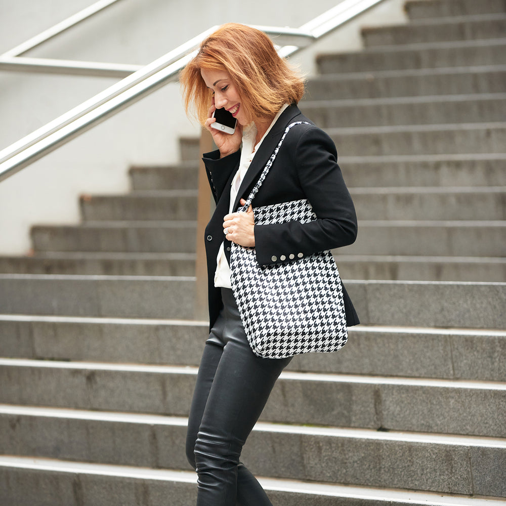 Woman on phone walking down train station steps carrying Black and White Houndstooth Shoezie Shoe tote bag