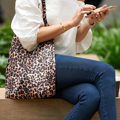 Woman sitting, playing on phone with Leopard Print Shoezie shoe tote bag over shoulder