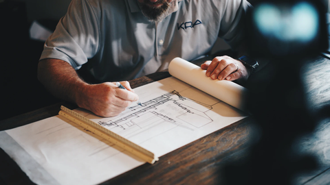 Architect looking over designs on a table.