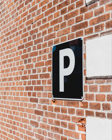 Alt Text: a Parking sign posted on a brick wall