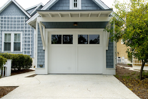 blue paneled house with white garage