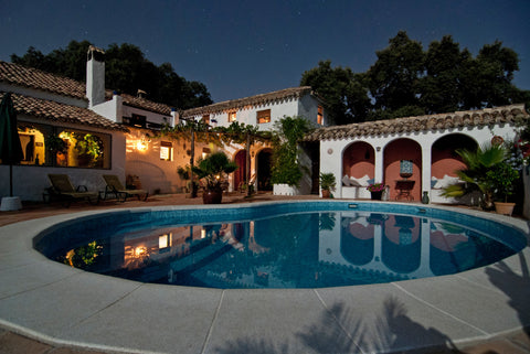 backyard pool at night with outdoor lights