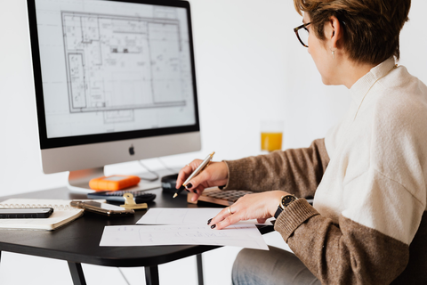 A woman studying floor plans on a computer screen.on Your House