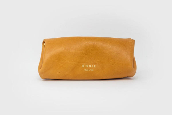 Long tan leather purse with gold embossed Bindle logo on grey background